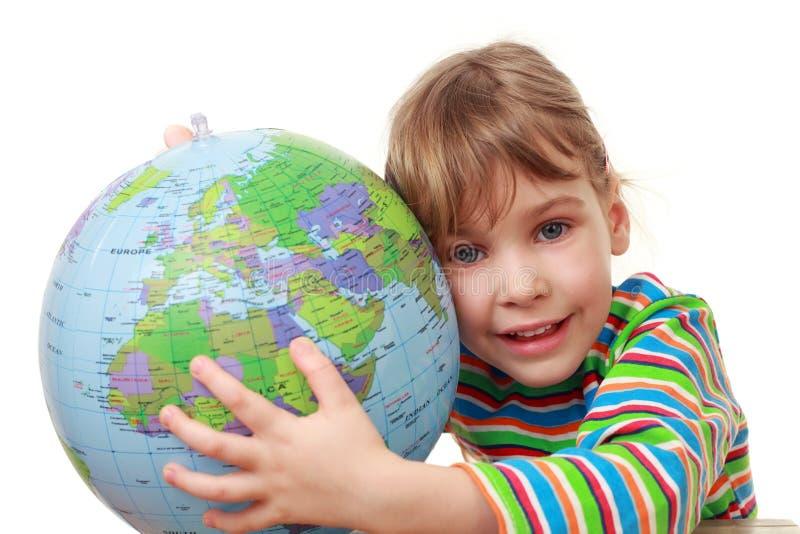 Petite fille dans la pièce de chemise avec le globe gonflable images libres de droits