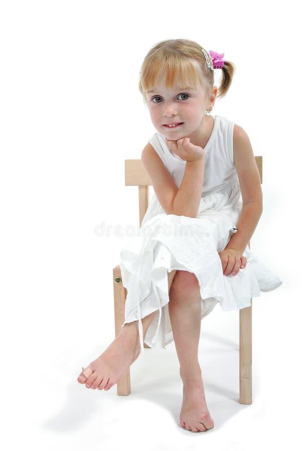 Petite fille dans la robe blanche se reposant sur la présidence images stock