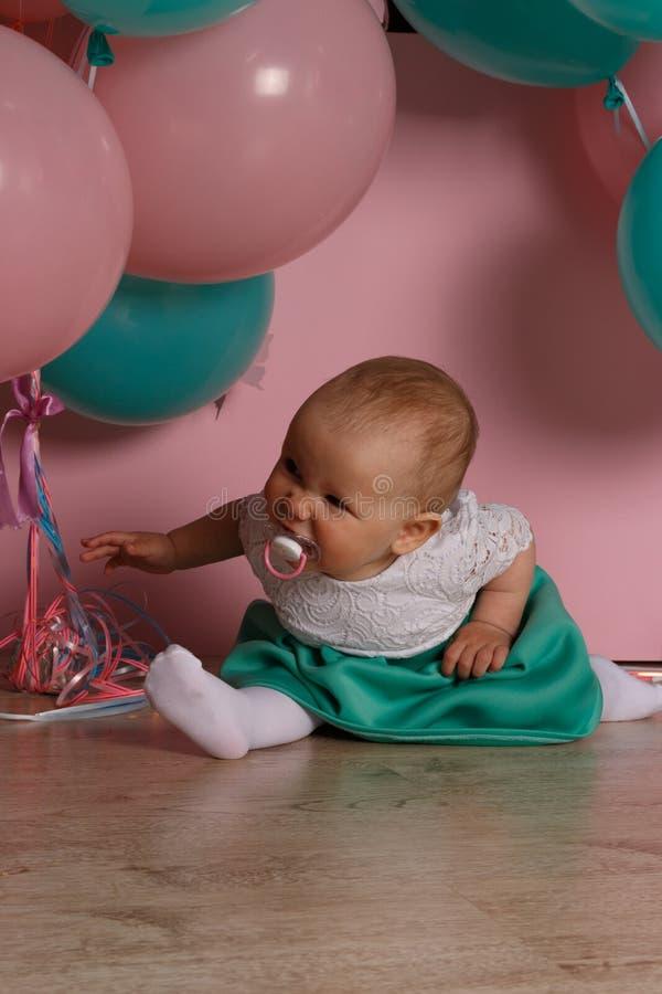Petite fille dans la robe bleue et blanche à côté des ballons, souriant, vacances, année, enfant d'anniversaire repose sur le pla photos libres de droits