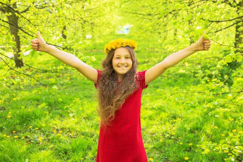 Petite fille dans la robe et la couronne rouges des pissenlits montrant des pouces photo stock