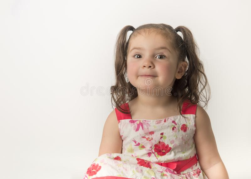 Petite fille dans la robe fleurie sur le fond blanc images stock