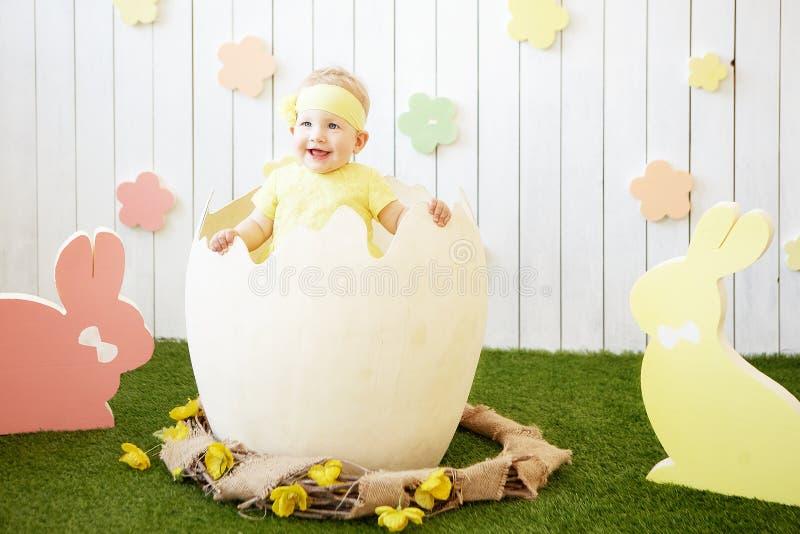 Petite fille dans la robe jaune à la coquille d'oeuf et aux lapins autour image libre de droits