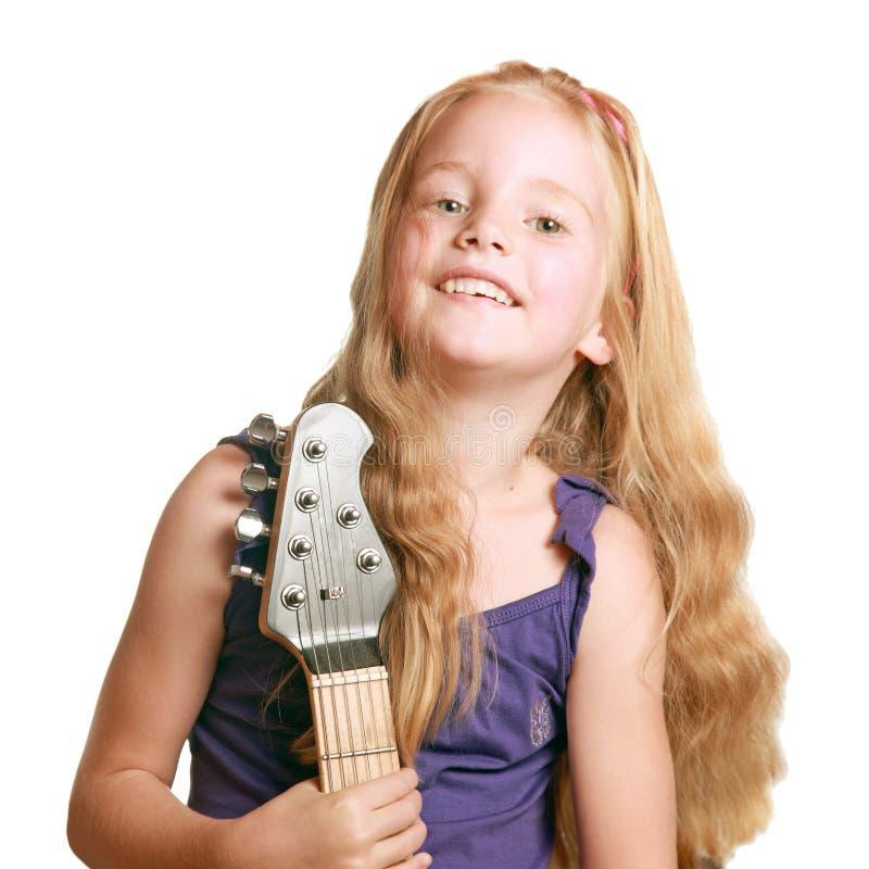 Petite fille dans la robe pourpre avec la guitare électrique image stock