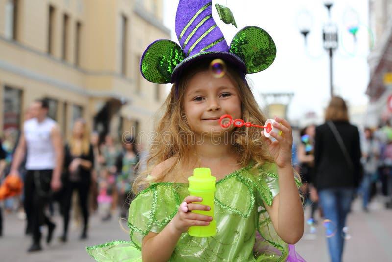Petite fille dans la robe verte de fantaisie jouant avec des bulles de savon images stock