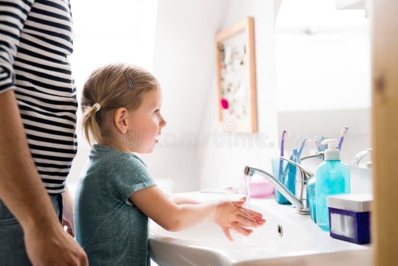 Petite fille dans la salle de bains avec les mains de lavage de père photos stock
