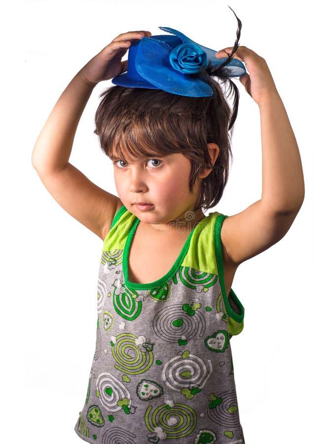 Petite fille dans le chapeau bleu minuscule d'isolement sur le fond blanc photo stock