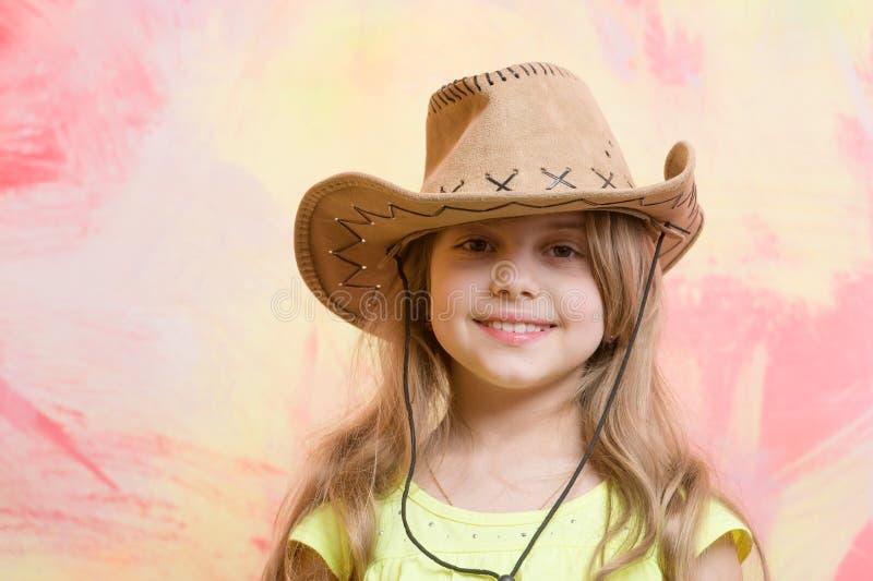 Petite fille dans le chapeau de cowboy sur le fond coloré, l'espace de copie photos libres de droits