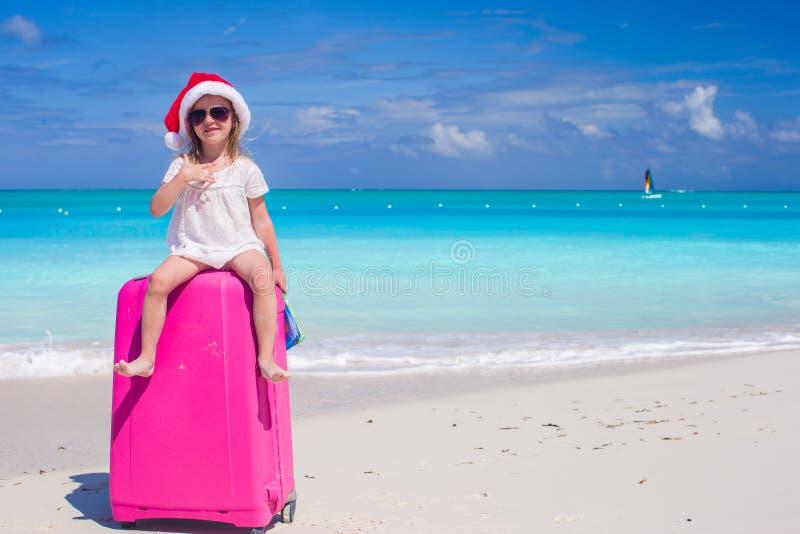 Petite fille dans le chapeau de Santa se reposant sur une grande valise à la plage tropicale photo stock