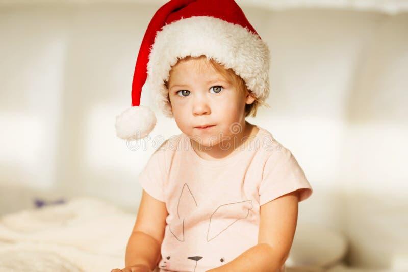 Petite fille dans le chapeau de Santa Verticale de beau bébé photographie stock