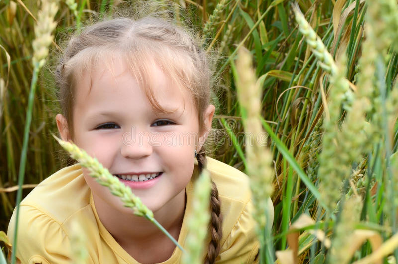 Petite fille dans le domaine blond comme les blés image stock