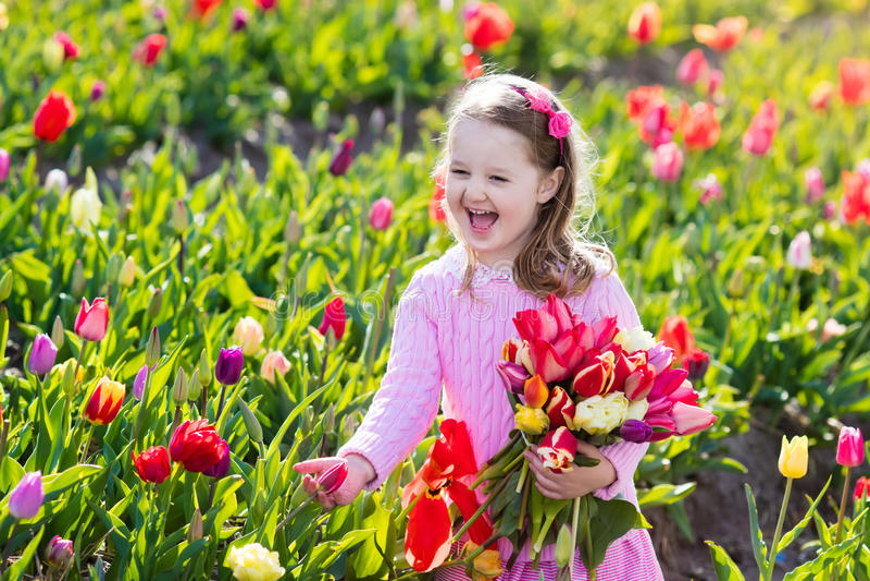 Petite fille dans le jardin d'agrément de tulipe photos libres de droits