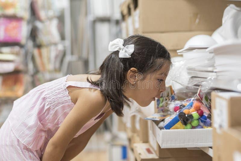 Petite fille dans le magasin regardant le matériel de métiers pour le travail photo libre de droits