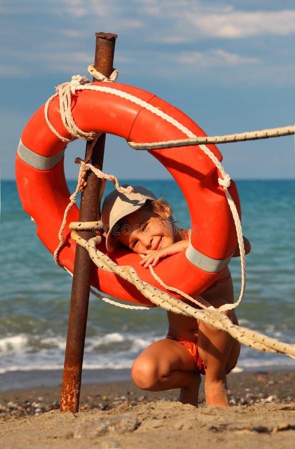 Petite fille dans le maillot de bain restant sur la plage photographie stock libre de droits