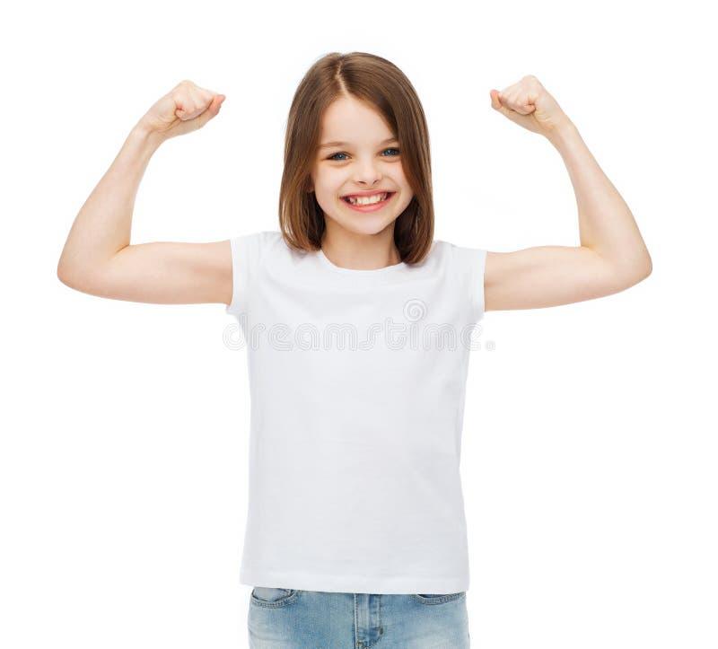 Petite fille dans le T-shirt blanc vide montrant des muscles photos stock