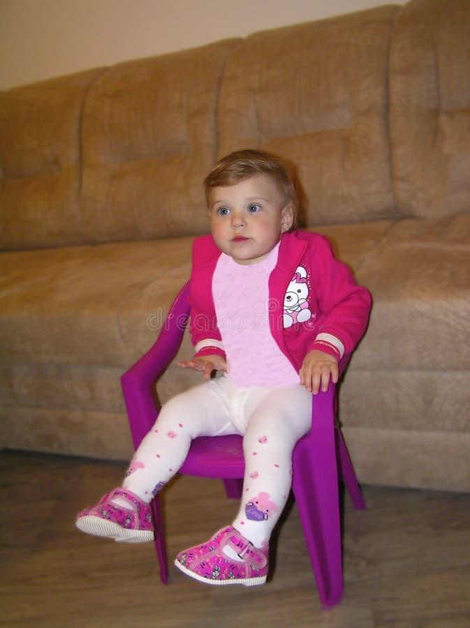 Petite fille dans un chemisier rouge se reposant sur la chaise image libre de droits