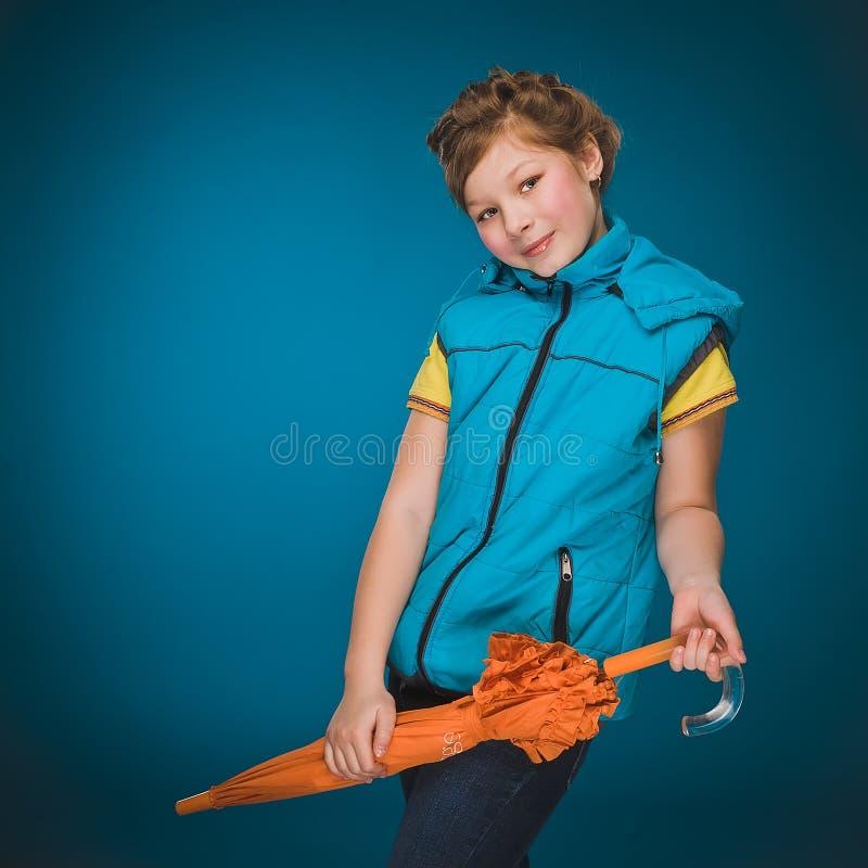 Petite fille dans un gilet avec un parapluie orange photographie stock libre de droits