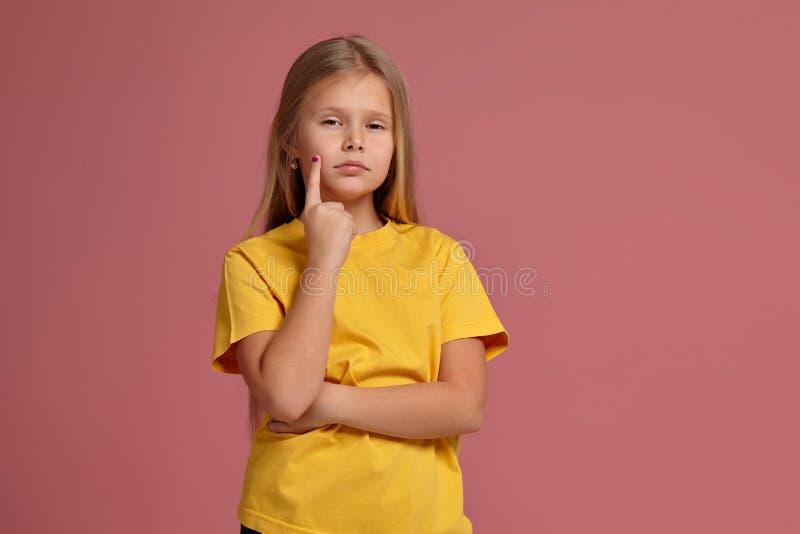 Petite fille dans un T-shirt jaune montre pensivement le doigt photos libres de droits