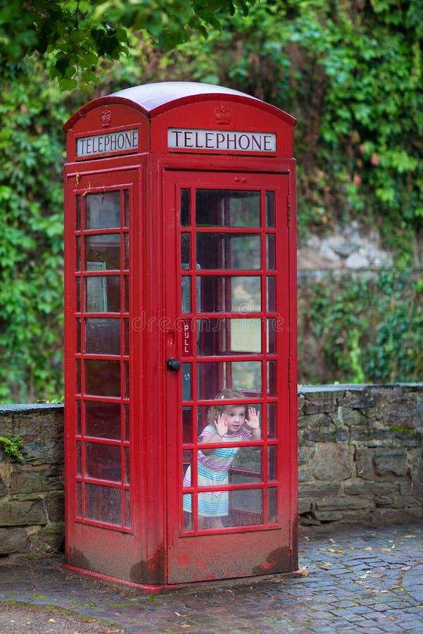 Petite fille dans une cabine téléphonique photos libres de droits