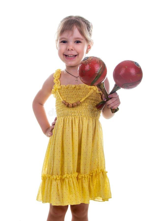 Petite fille dans une robe jaune lumineuse tenant des maracas dans des ses mains Photo de studio, fond blanc lumineux photographie stock libre de droits