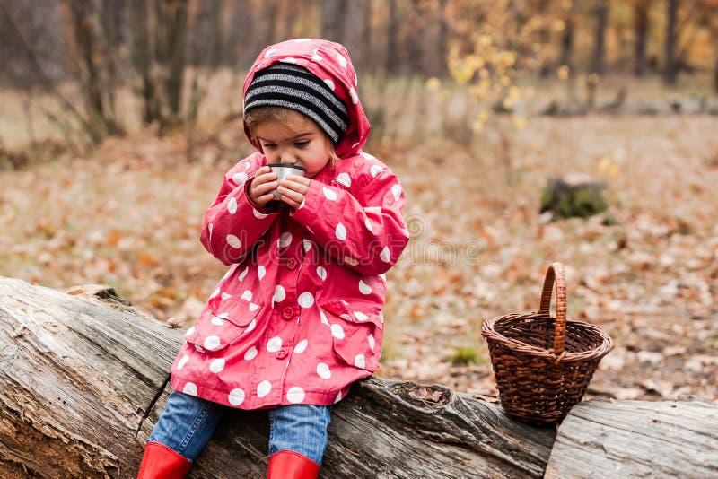 Petite fille dans une veste de pois se reposant sur un arbre et un thé potable photographie stock
