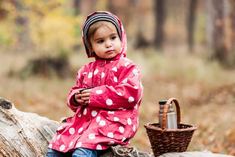 Petite fille dans une veste de pois se reposant sur un arbre et un thé potable images libres de droits