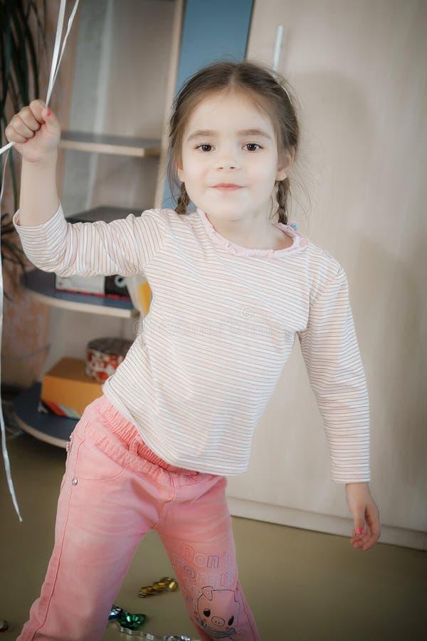 Petite fille dansant à la maison et visages de poses images stock