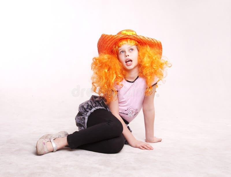Petite fille de beau roux s'asseyant dans le studio photo stock