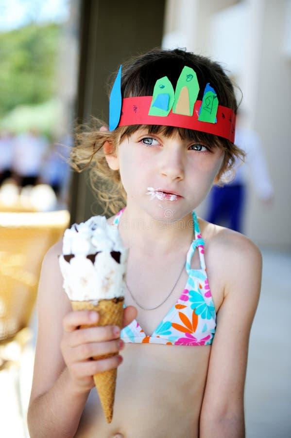Petite fille de brune mignonne mangeant la crème glacée  photographie stock