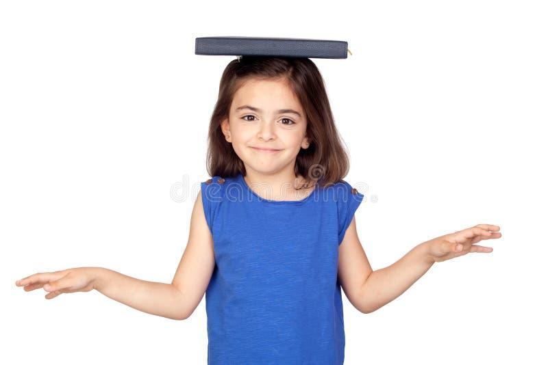 Petite fille de Brunette avec un livre sur sa tête image libre de droits