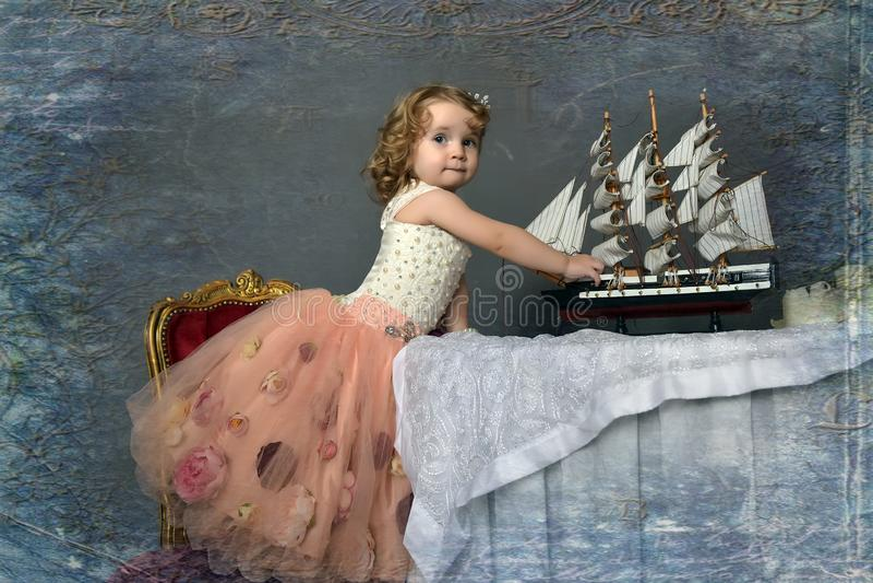 Petite fille de charme dans le blanc élégant avec se reposer rose de robe photographie stock libre de droits