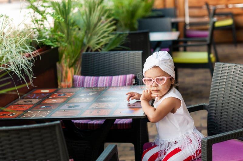 Petite fille de charme réfléchie avec un turban blanc sur sa tête à une table dans un café photos libres de droits