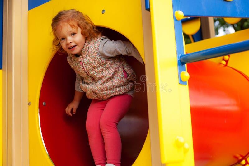 Petite fille de cheveux rouges rampant par le tunnel dans le terrain de jeu photos stock