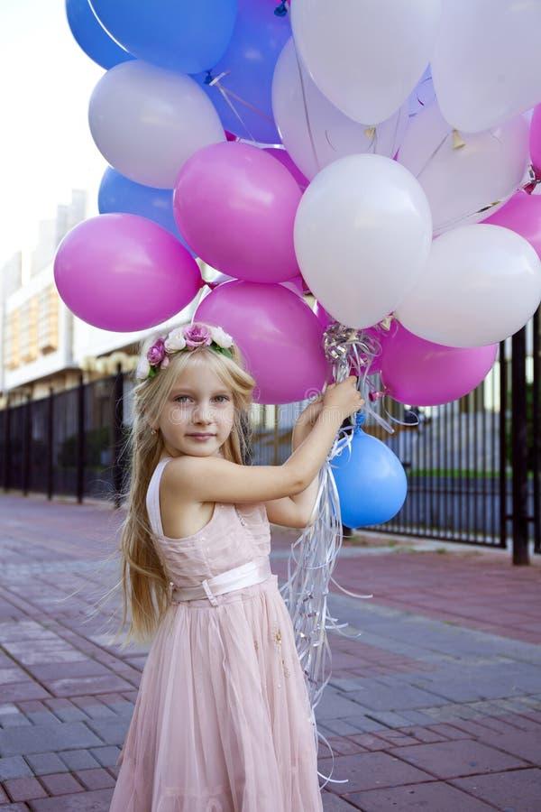 Petite fille de cinq ans dans une robe rose tenant des ballons image libre de droits