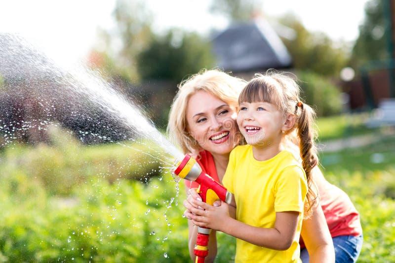 Petite fille de jardinier avec la mère arrosant sur la pelouse près de la maison photos libres de droits