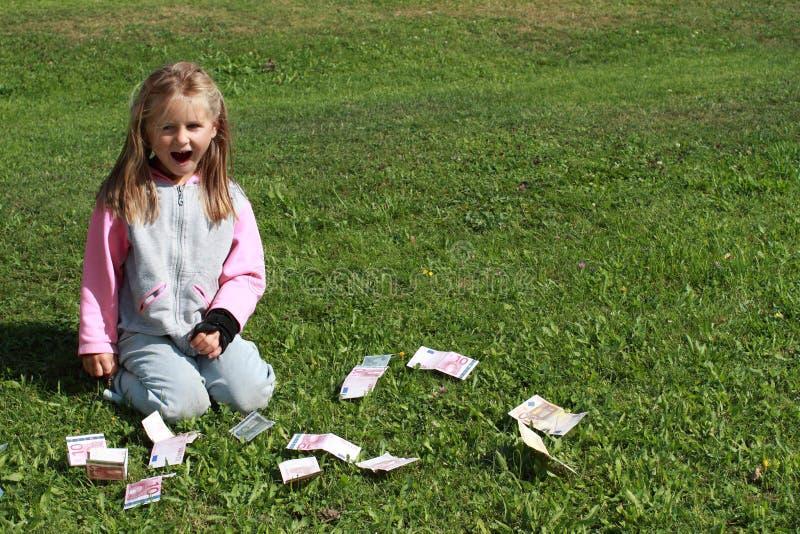 Petite fille de Kneeing avec de l'argent autour photos libres de droits