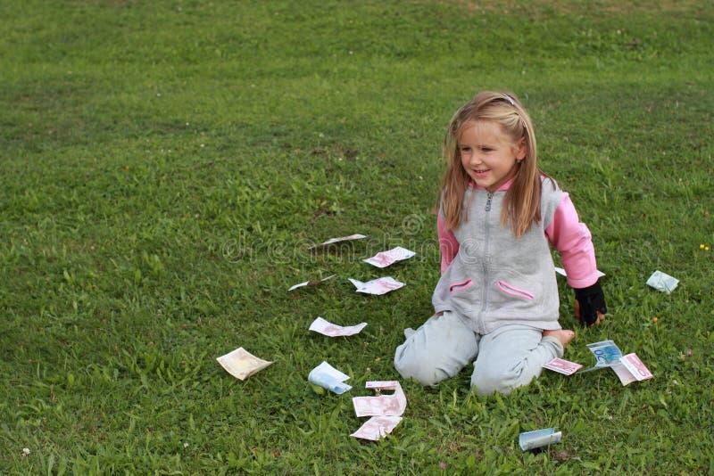 Petite fille de Kneeing avec de l'argent autour photographie stock libre de droits