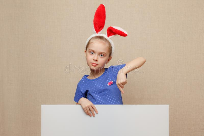 Petite fille de lapin dirigeant son doigt sur une bannière vide de livre blanc photographie stock