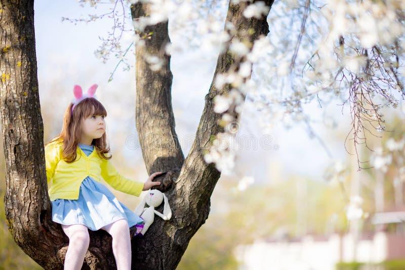 Petite fille de lapin dr?le adorable s'asseyant aux trois de floraison ? la journ?e de printemps ensoleill photo stock
