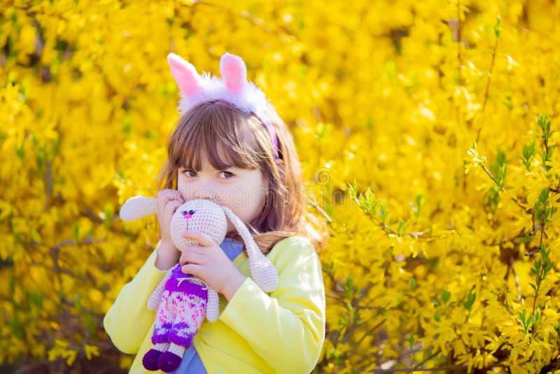 Petite fille de lapin dr?le adorable tenant le jardin de fleur de jouet de lapin au printemps images stock