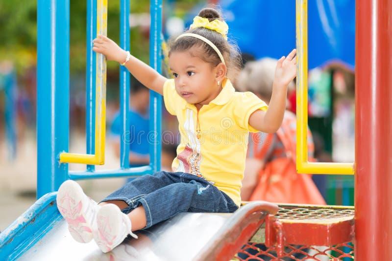 Petite fille de métis employant une glissière à un terrain de jeu photographie stock