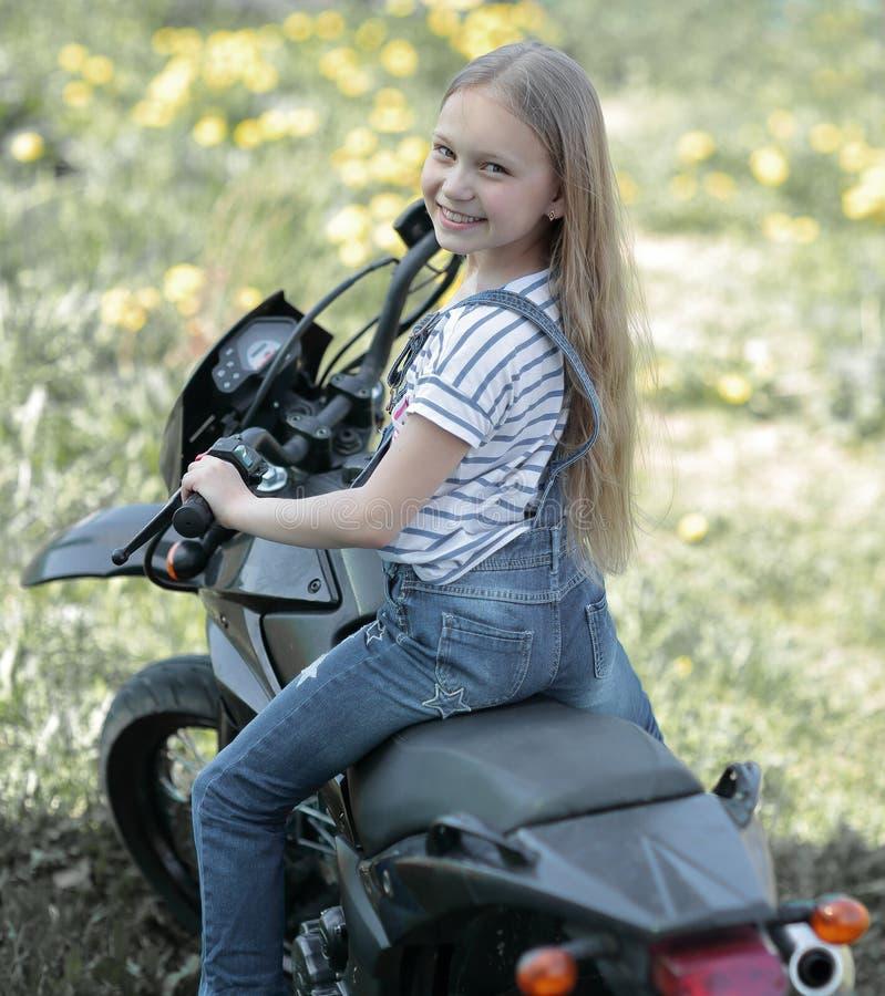 Petite fille de motard montant sa moto image libre de droits