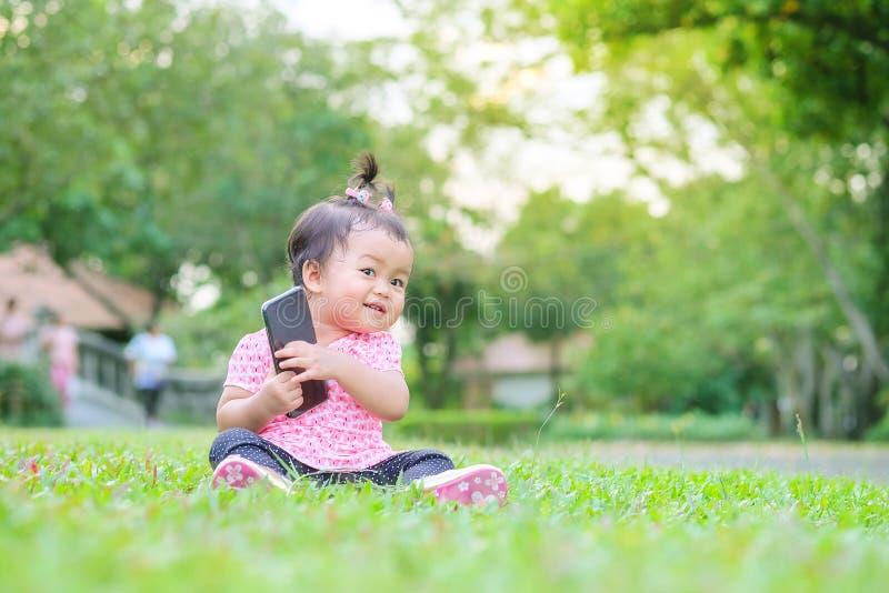 Petite fille de plan rapproché se reposer sur le plancher d'herbe en parc avec le fond de lumière du soleil dans le mouvement mig photos libres de droits