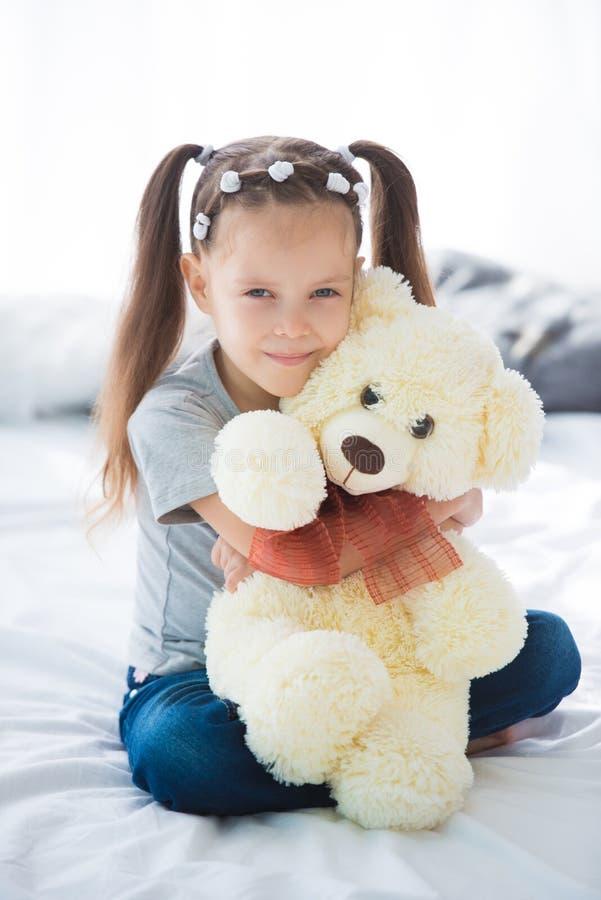 Petite fille de sourire adorable s'asseyant sur un lit étreignant un ours de nounours blanc photographie stock