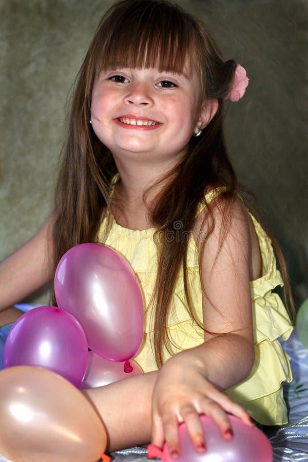 Petite fille de sourire avec des ballons photos libres de droits