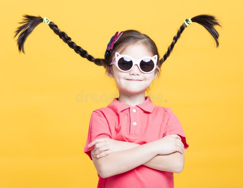 Petite fille de sourire avec des lunettes de soleil image libre de droits