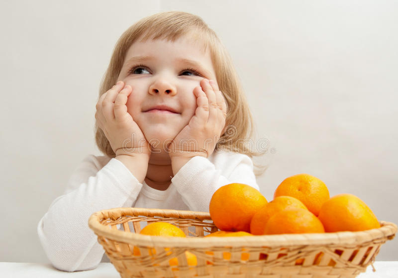 Petite fille de sourire avec des mandarines photos stock