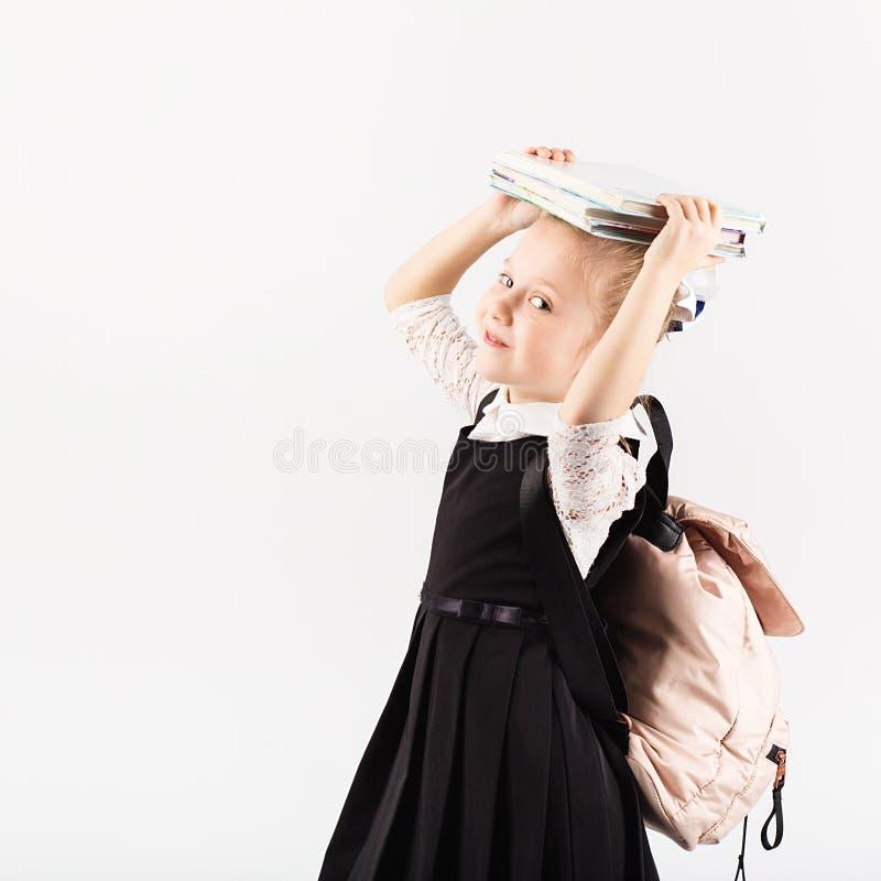 Petite fille de sourire avec le grand sac à dos tenant des livres contre le petit morceau photographie stock