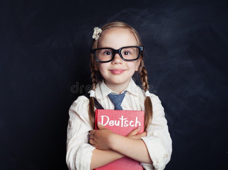 Petite fille de sourire avec le livre allemand photographie stock