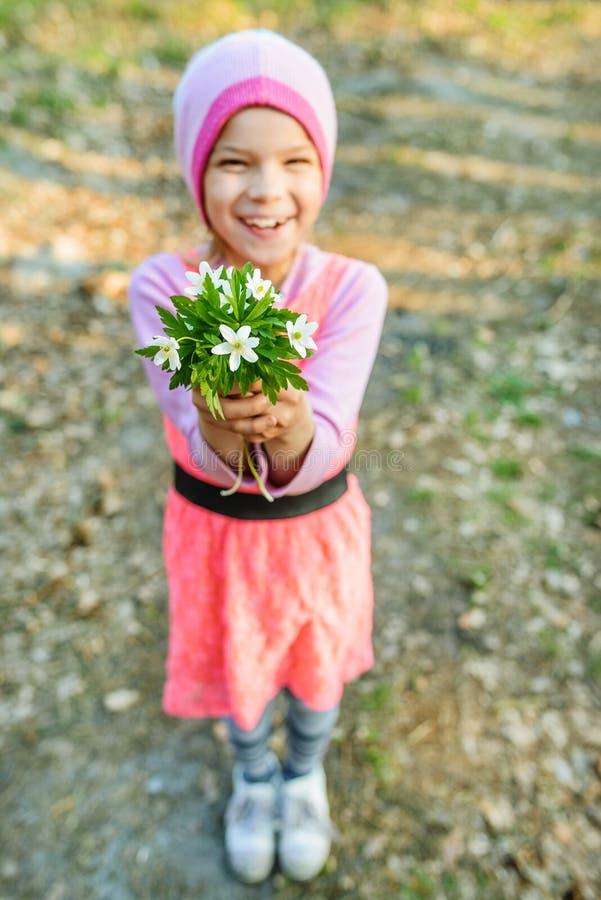 Petite fille de sourire avec le nemorosa d'anémone photo libre de droits