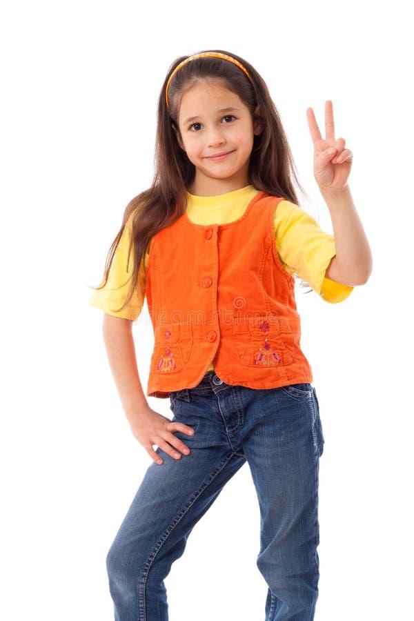 Petite fille de sourire avec le signe de victoire images stock